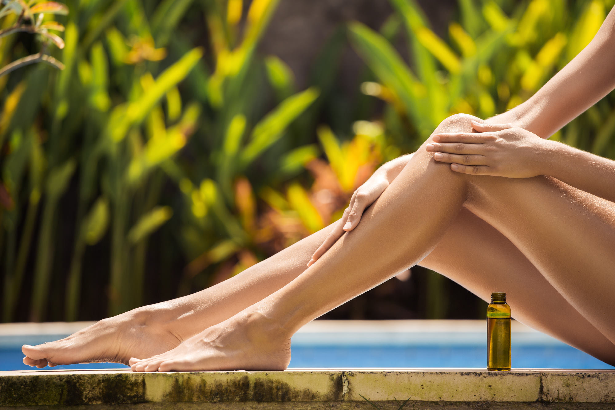 Young slim beautiful woman in bikini applying oil for sun protection.